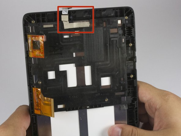 Carefully gripping the top of the camera connection cord, slowly pull down to remove the sticky tape from the tablet.