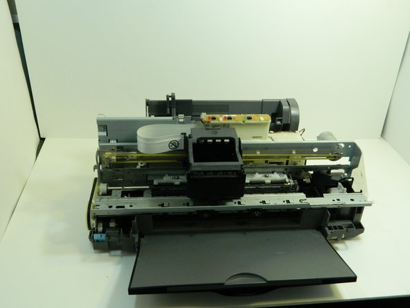 Gently pull the plastic housing upward to remove the back panel and reveal the inner components of the printer.