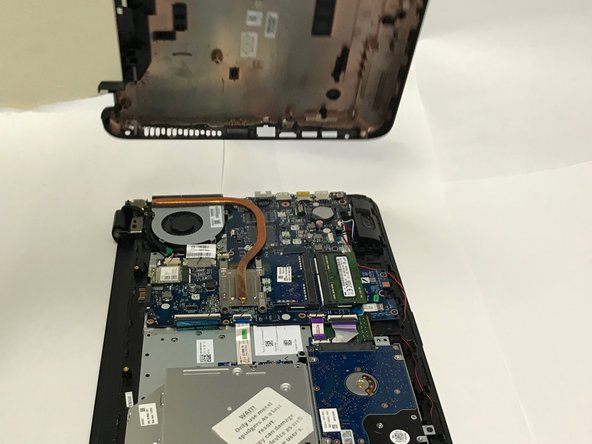 Using the prying tool, wedge it underneath the back of the laptop and do the same all around until the back comes off.