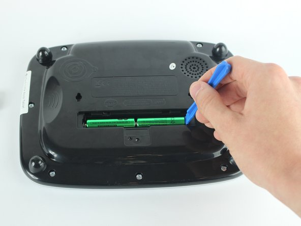 Use a plastic opening tool to pry the batteries out of their holding.