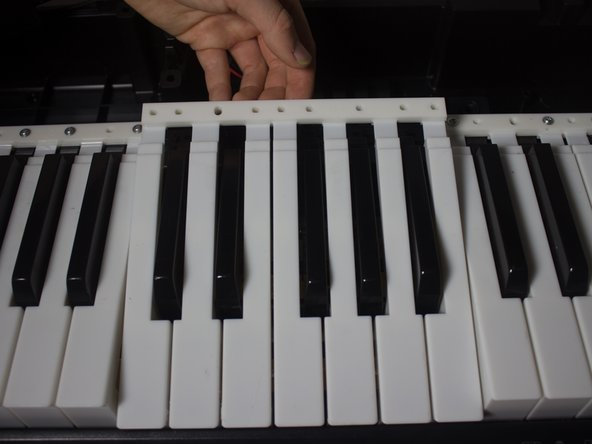 You will be able to pick up the white keys with your hands and remove them.