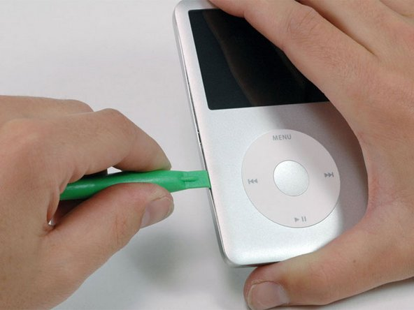Image 1/1: Insert a plastic opening tool into the seam between the front and back of the iPod.