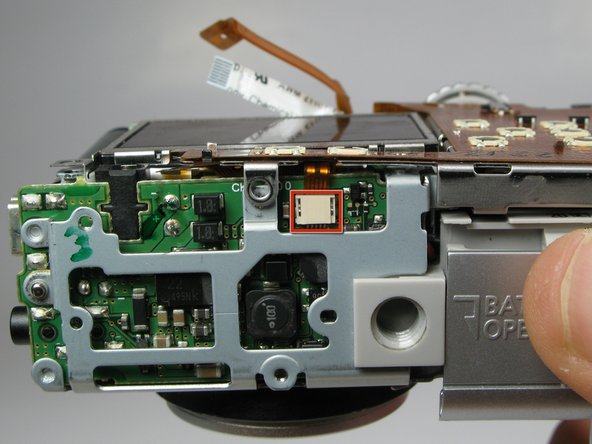Locate the copper ribbon cable attaching the LCD screen to the bottom motherboard.