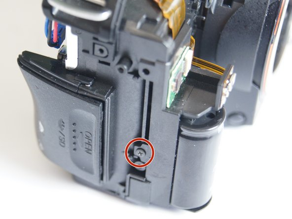 Remove the 5.0 mm Phillips #00 screw on the left side of the camera next to the flash capacitor.