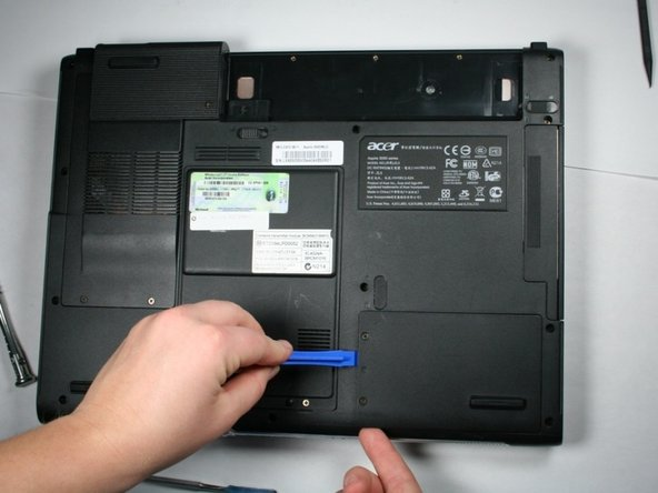 Insert the plastic opening tool under left side of the hard drive cover and gently pry the cover open.