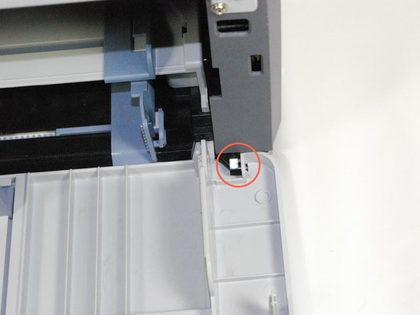 Remove front panel by gently moving the holes on the panel from the pegs attached to the main printer body, one at a time.