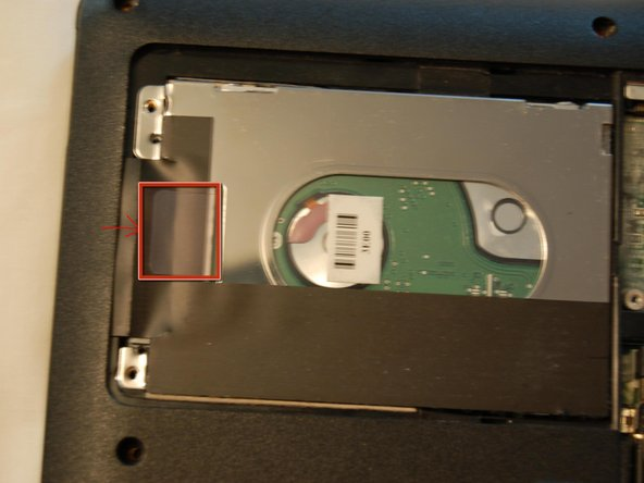 Lift out the hard drive by grasping the plastic tab and pulling gently.  Place in an anti-static bag.