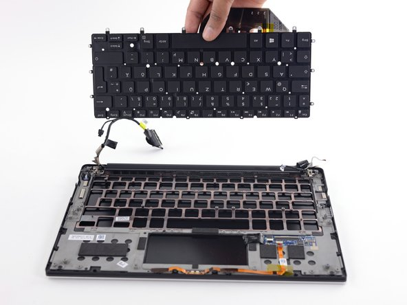 Image 3/3: And after removing a couple dozen more screws, the keyboard comes out with no drama (and no tape!).
