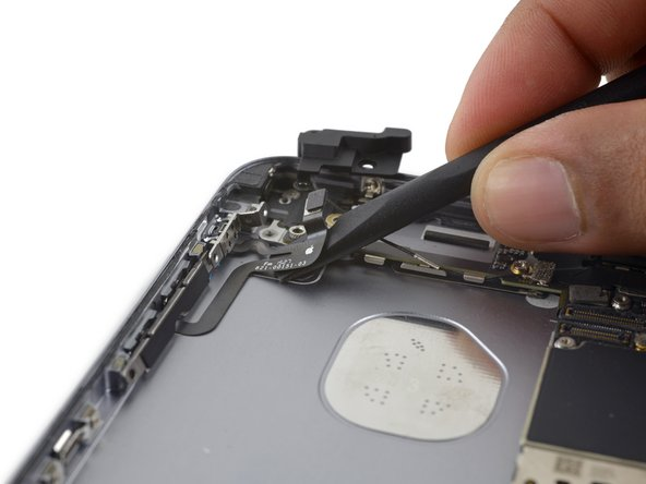Use the flat end of a spudger to peel the volume control flex cable off the rear case.