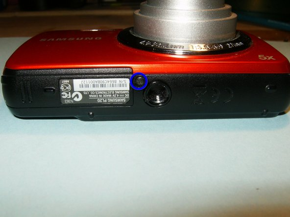 Image 1/3: Remove the two screws on the side of the the device, to the right of the camera lens.