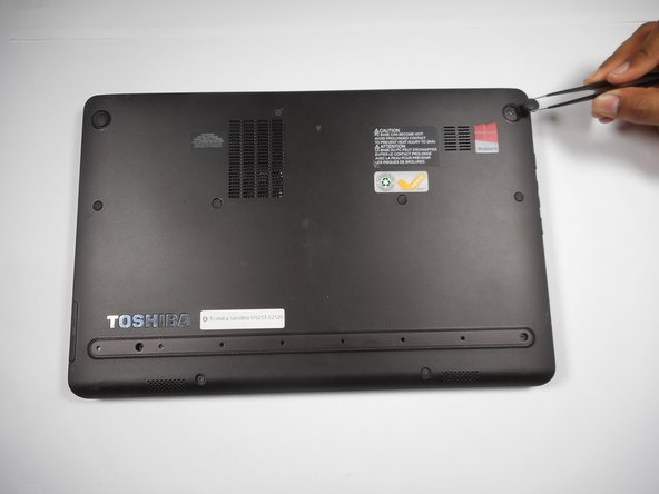 Use tweezers to pinch and pull out and remove the nine rubber gripper pads on the back panel of the laptop. Set aside.
