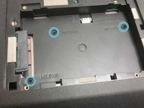 Unscrew the two captive screws securing the RAM/HDD door to the base.