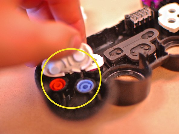 Then lifting these pads will give you access to the four front buttons (circled in yellow), and D-pad (circled in red).