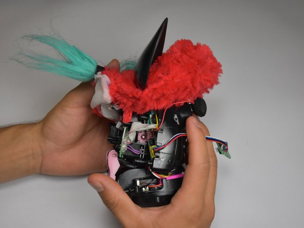 Orient the Furby with the tail pointing left and the face pointing right.