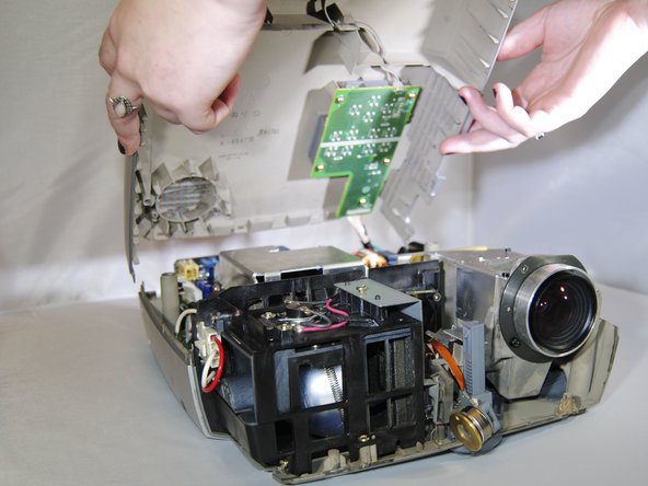 Being careful not to pull the wires inside the projector, gently lift the top panel off the projector.