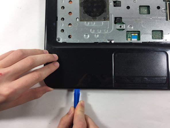 Insert the plastic opening tool into the seam between the palm rest and the laptop.