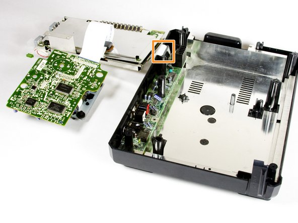 Carefully lift off the metal plate, the motherboard, and the CD tray circuit board. Then,  flip each piece over, as pictured.