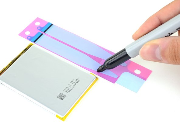 Using a pen, mark a line on the stretch release adhesive just slightly above the bottom edge of the battery.