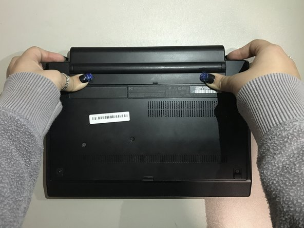 Use your fingers to push both battery release tabs on the back of the computer.