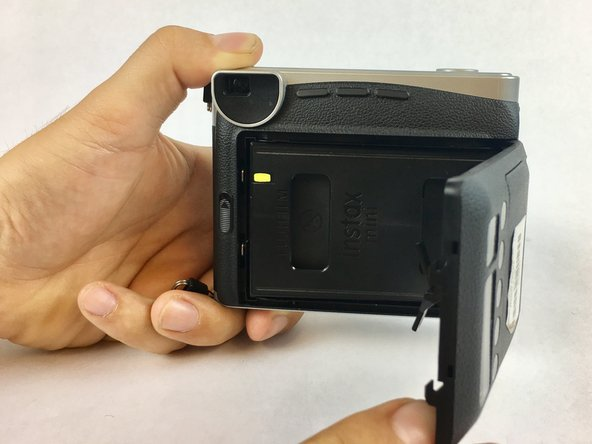 Open up the back side of the camera by pushing up on the slide button. This button is located on the middle left side of the camera.