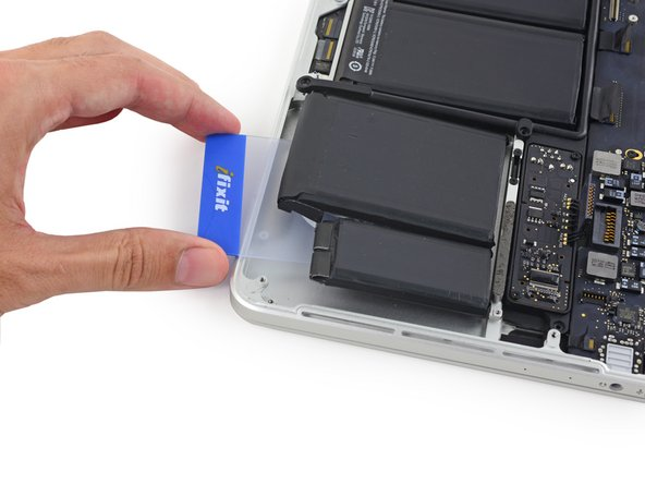 Temporarily leave your plastic card underneath the two rightmost battery cells to prevent them from re-adhering to the upper case.