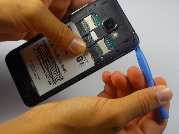 Insert the plastic opening tool into a corner of the plastic panel and gently pry it away from the rest of the phone.