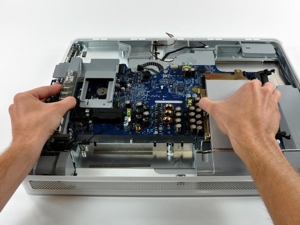 Image 1/2: Lift the logic board out of the midplane. Careful, there is a light guide on the lower left that can tear if you are not careful. This guides the light to the power-on light at the front of the iMac.