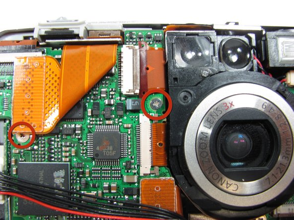 Remove the 3.3mm screw halfway up the left side of the motherboard just to the left of the lens.