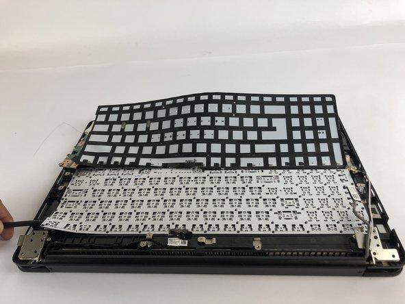 Insert black Spudger in bottom left corner and lift the keyboard up.