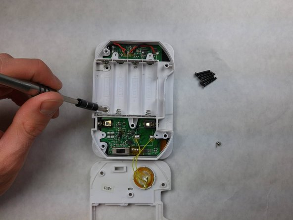 Image 1/3: Remove the metal terminals from the battery slot closest you.