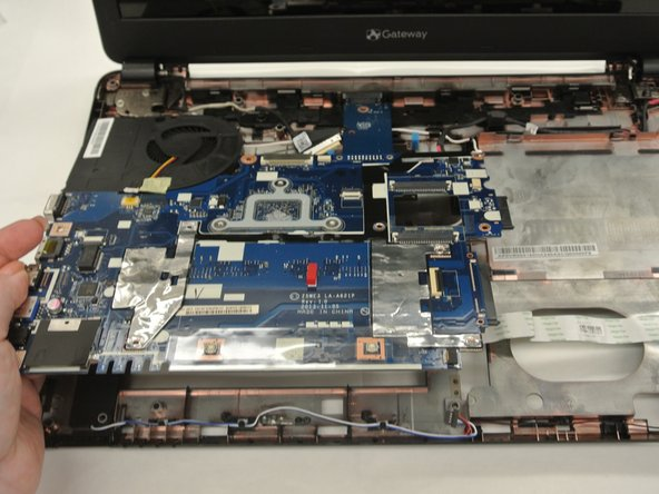 Lift the motherboard up and out of the casing and pull it away from the screen in order to partially detach it from the laptop.