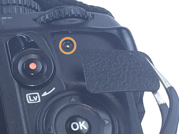 Image 2/2: Remove one 3mm screw behind the rubber grip on the top right of the back panel.