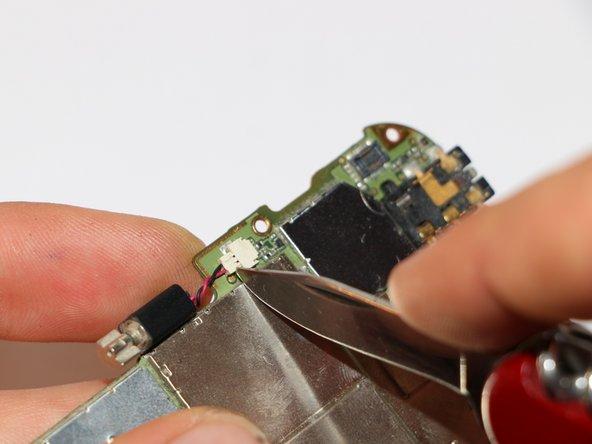 Löse mit einem Messer oder einer Pinzette den Vibrationsmotor. Dabei gilt wieder: Nicht an den Kabeln, sondern an der Plastikkontaktstelle vorsichtig abziehen.