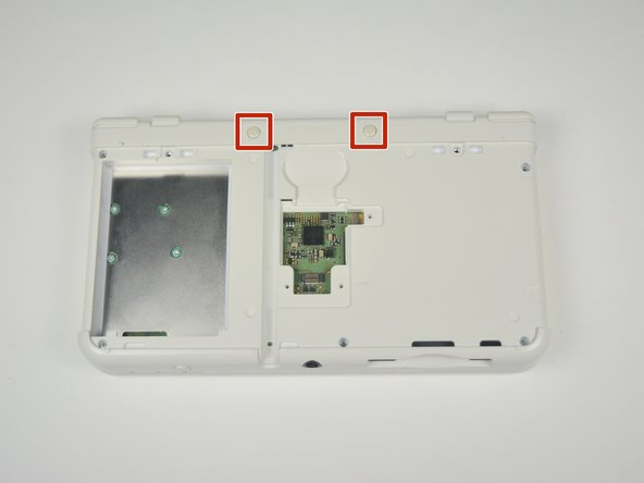 Image 1/3: Remove the two rubber bumpers along the top of the device using tweezers.