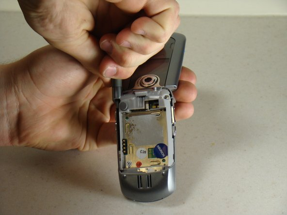 Image 1/2: Pull the apparatus up and out of the phone.