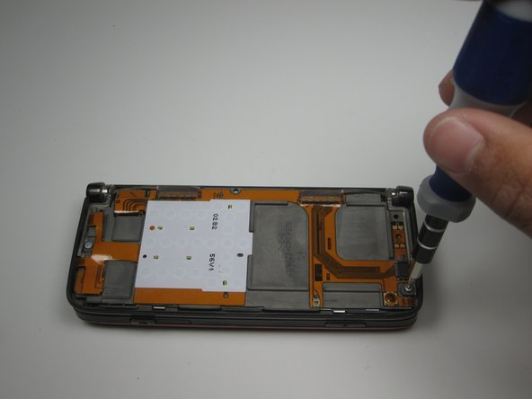 Using the T5 Screwdriver, remove the two screws shown.