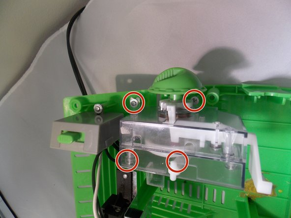 There are four screws (circled in red) that need to be removed with a Phillips #00 Precision screwdriver.