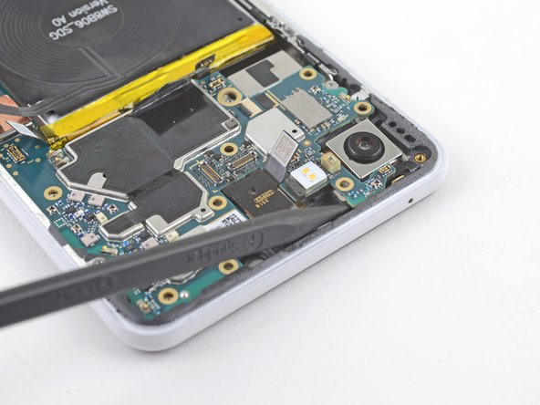 Insert the point of a spudger underneath the motherboard, near the rear-facing camera module.
