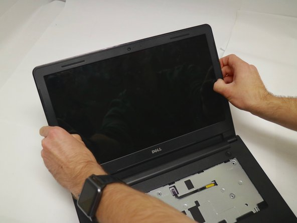 Using your fingertips, gently pry up the inner edges of the display bezel.