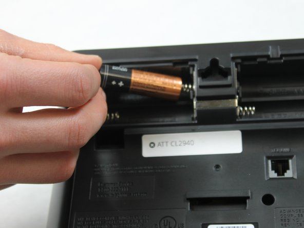 Place four AA batteries in the battery compartment. Position the negative end (-) at the side with the spring as shown.