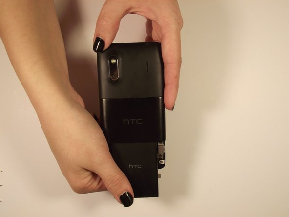 Image 2/2: Grab the bottom edge of the battery and pull it toward you