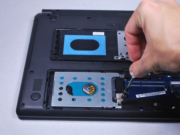 Use a PH0 Phillips screwdriver to remove the screw securing the hard drive.