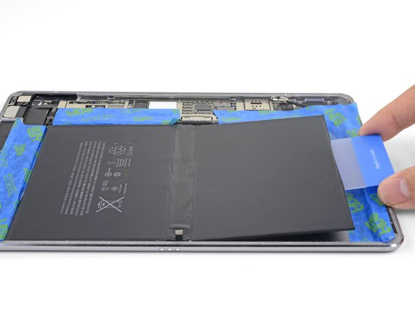 Use the plastic card or your fingers to flip the bottom half of the battery over so that it rests on top of the upper half.