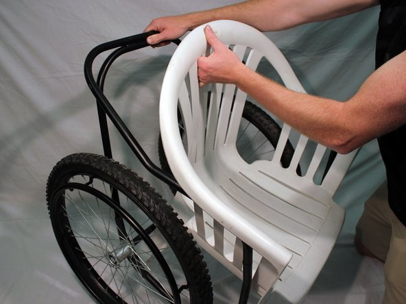 Remove the lawn chair from the back frame by lifting it up.