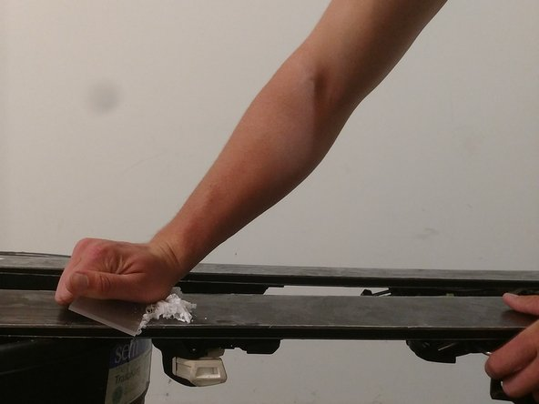 Scrape the excess wax off with the plastic scraper. Continue this process until there is no visible wax on the ski base.