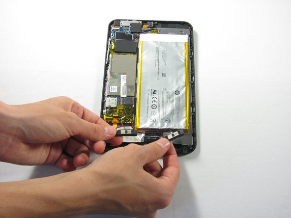 Remove the two speakers at the bottom of the device using tweezers.