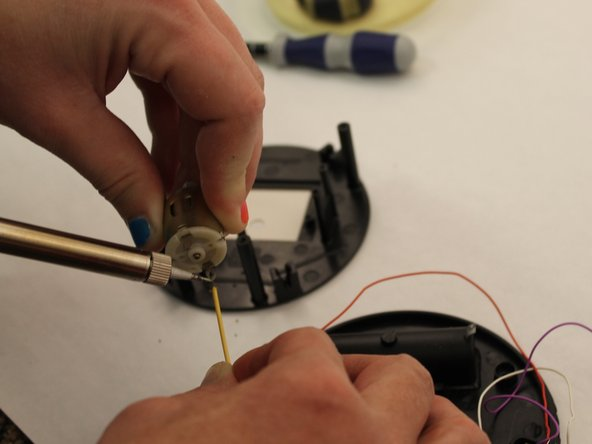 Using soldering iron, detach wire end from the copper cylinder by plaint the end of the iron to the end of the wire. Now you can replace the alarm switch with a new one by attaching one end of the wires to the copper cylinder . Then install the switch screws using the screwdriver.