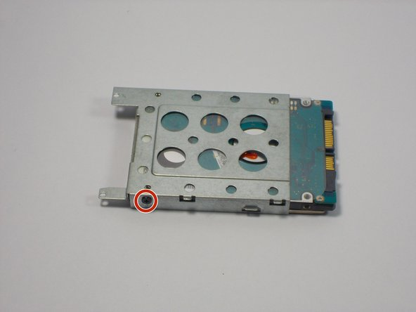 Remove two 3mm Phillips head screws, one located on each side of the metal casing holding the hard drive using the PH0 bit.