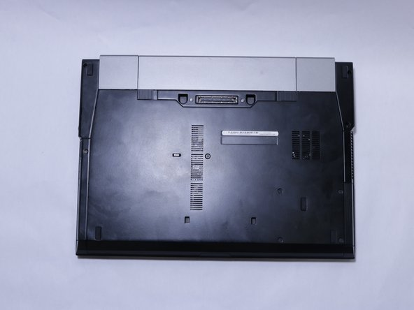 Turn laptop over with the hinges facing away.