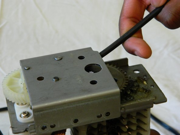 Use a metal spudger to pry the bracket from the main shredder assembly.